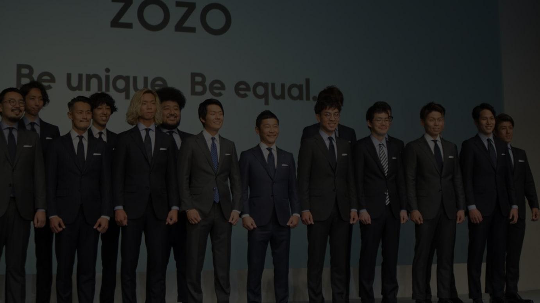 ゾゾのビジネススーツを着用して発表会に登壇した前澤友作代表取締役社長(中央)とスタートトゥデイ社員(2018年撮影)