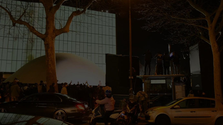 ショーの様子をひと目見ようと会場外ではバス停の上に上がる人も。